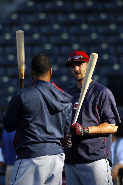 Cleveland Indians' Carlos Santana, left and Lonnie Chisenhall, right, chat during batting practice before a baseball game against the Kansas City Royals at Kauffman Stadium in Kansas City, Mo., Thursday, July 24, 2014. (AP Photo/Colin E. Braley)