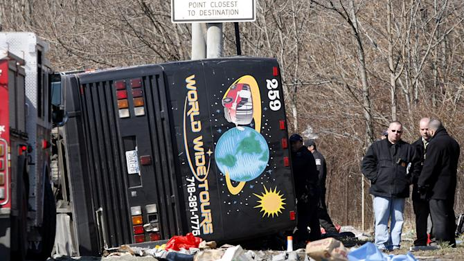 FILE - In this March 12, 2011, file photo, emergency personnel investigate the scene of a bus crash on Interstate 95 in the Bronx borough of New York. Safety officials are planning to release Tuesday, June 5, 2012, the results of an investigation into a deadly tour bus crash in New York last year that killed 15 passengers and helped prompt a crackdown on rogue bus operators by federal regulators. (AP Photo/David Karp, File)