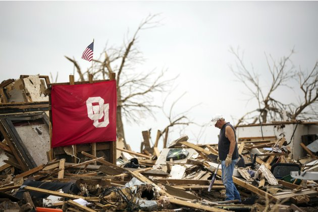 Richard Nichols stops to look for items to salvage in his son's home several days after it had been destroyed by a tornado in Moore, Oklahoma