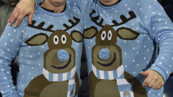 Fans wear Christmas jumpers during the English Premier League soccer match between Manchester City and West Bromwich Albion at The Hawthorns in West Bromwich