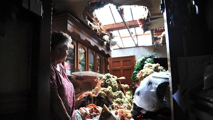 Faye Busby looks over her living room after a tornado ripped part of the roof off of her home in Graysville, Ala. on Tuesday, April 29, 2014. A strong line of tornado-producing storms made its way across the southeast Monday causing damage in the area. (AP Photo/AL.com, Tamika Moore)