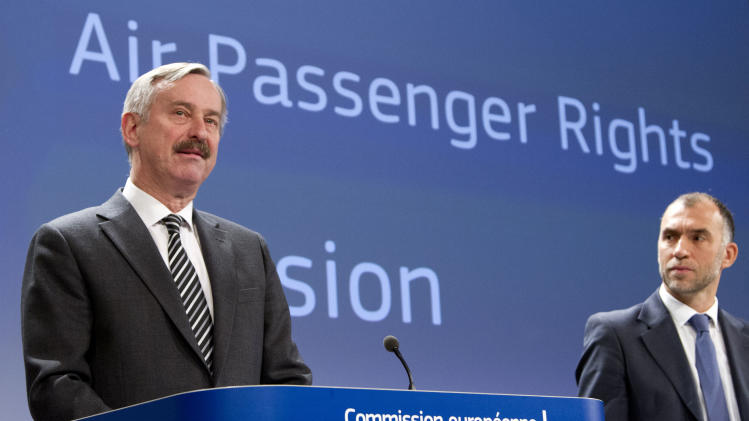 European Commissioner for Transport Siim Kallas, left, speaks during a media conference at EU headquarters in Brussels on Wednesday, March 13, 2013. The European Union is considering beefed up measures for stranded passengers to get compensation and find quicker ways to get home. Man at right unidentified. (AP Photo/Virginia Mayo)