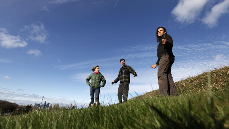 "In this March 3, 2012 photo, Briar Bates, left, Glenn Herlihy and Jackie Cramer stand on a grassy slope and talk about how they and other organizers will turn the site into a ""food forest"" in view of downtown Seattle. The park will start at 2 acres and grow to 7, offering city dwellers a chance to pick apples, plums and other crops right from the branch.     (AP Photo/Elaine Thompson)"