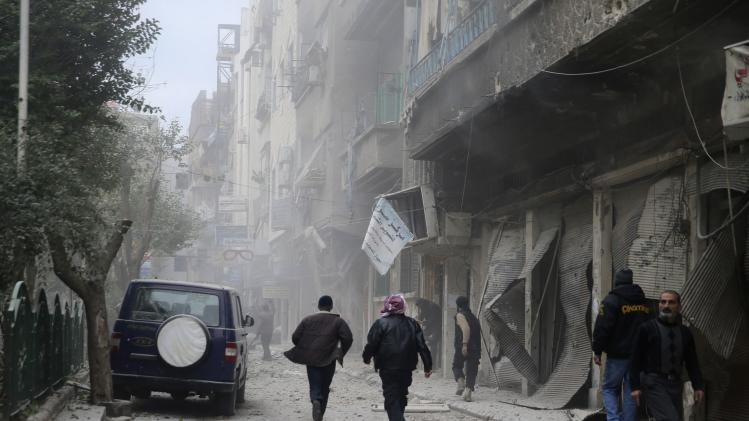 People run at a site hit by what activists said was an air raid by forces loyal to Syrian President Assad in Damascus
