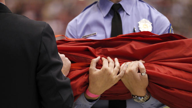 Members of the St. Louis fire and police departments hold a field-length flag as part of a pregame ceremony on the 10th anniversary of the 9/11 terrorist attacks before the start of an NFL football game between the St. Louis Rams and the Philadelphia Eagles, Sunday, Sept. 11, 2011, in St. Louis. (AP Photo/Jeff Roberson)