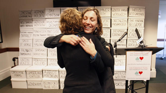 FILE - In this Jan. 26, 2012, file photo, Ali Vanderzanden, political director for Equality Maine, hugs a friend before a news conference at the State House in Augusta, Maine. Dozens of boxes in the background contains more than 105,000 signatures collected by supporters of gay marriage to force a second referendum on the issue. Poll after poll shows public support for same-sex marriage steadily increasing, to the point where it's now a majority viewpoint. Yet in all 32 states where gay marriage has been on the ballot, voters have rejected it. It's possible the streak could end in November 2012, when Maine, Maryland, Minnesota and Washington state are likely to have closely contested gay marriage measures on their ballots. For now, however, there remains a gap between the national polling results and the way states have voted.  (AP Photo/Robert F. Bukaty, File)