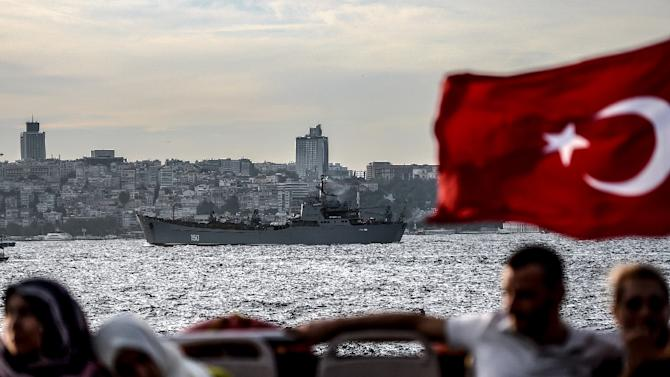 A Turkish flag flies on a ferry as Russian warship, the BSF Saratov 150, is seen sailing through the Bosphorus off Istanbul en route to the eastern Mediterranean sea