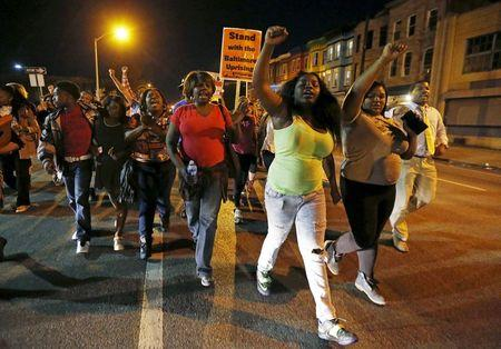 Protesters march down West North Avenue as they demonstrate against police brutality and celebrate the charges against the arresting officers in the death of neighborhood resident Freddie Gray in West Baltimore
