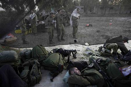 File picture of an Israeli soldier sleeping as others pray close to the ceasefire line between Israel and Syria on the Golan Heights