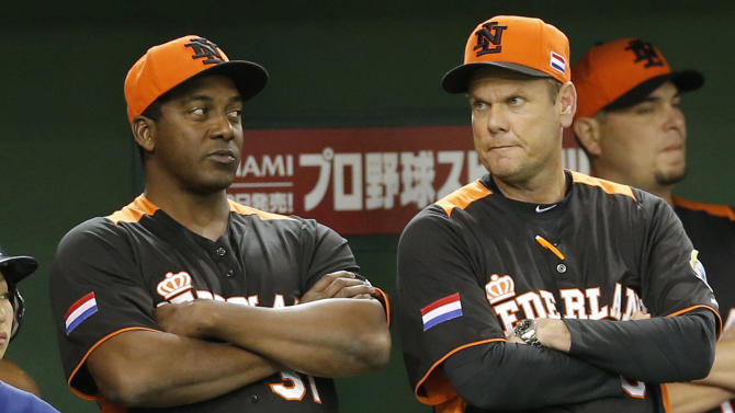 Netherlands' manager Hensley Meulens, left, and coach Robert Eenhoorn cross their arms at the dugout in the eighth inning of their World Baseball Classic second round game at Tokyo Dome in Tokyo, Tuesday, March 12, 2013. (AP Photo/Koji Sasahara)