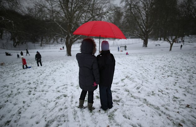 LONDON, UNITED KINGDOM - JANUARY 18: Women stand under a red umbrella as they watch their children play in fresh snow at Alexandra Palace on January 18, 2013 in London, England. Severe weather is expected in parts of the United Kingdom today.  (Photo by Peter Macdiarmid/Getty Images)