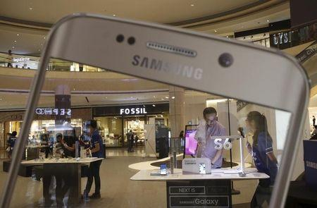People look at Samsung Galaxy phones during a prelaunch event in Singapore