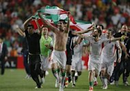 Iran's Hashem Beikzadeh (front 2nd L) holds the Iranian national flag as he celebrates with his teammates after defeating South Korea in their World Cup qualifying soccer match in Ulsan, southeast of Seoul June 18, 2013. REUTERS/Kim Hong-Ji