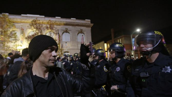 A protester records a video of police officers during a demonstration in Oakland