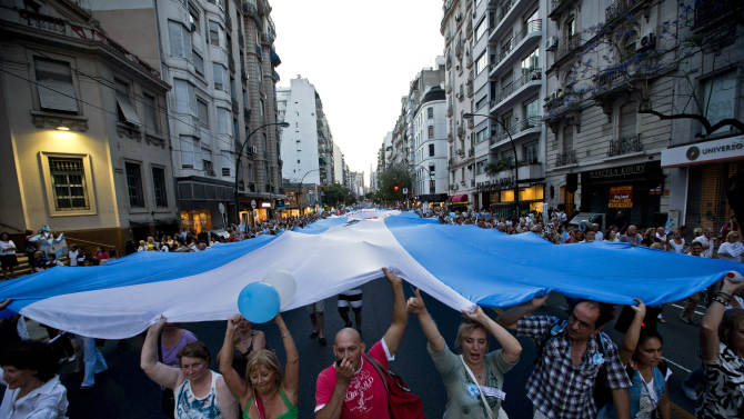 Protesters carry a large Argentine flag during an anti-government demonstration in Buenos Aires, Argentina, Thursday, Nov. 8, 2012. Thousands of people marched against rising inflation, crime, exchange controls and to express their fear to a constitutional reform that could open the way for a third consecutive reelection of Argentina's President Cristina Fernandez. (AP Photo/Victor R. Caivano)