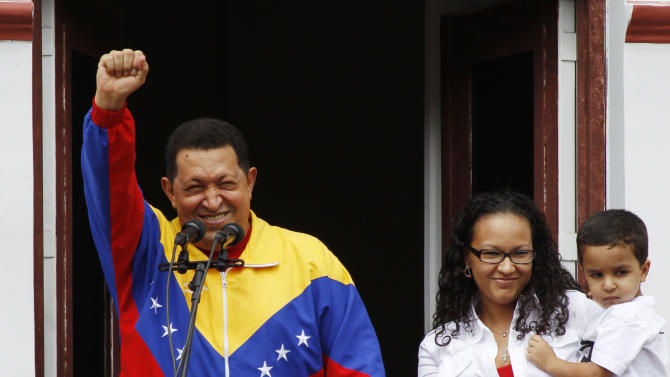 "FILE - In this May 22, 2011 file photo, Venezuela's President Hugo Chavez greets supporters next to his daughter Maria and grandson Jorge after his radio and television program ""Hello President!,"" his first public appearance after injuring himself while jogging two weeks earlier, at Miraflores presidential palace in Caracas, Venezuela. Venezuela's Vice President Nicolas Maduro announced on Tuesday, March 5, 2013 that Chavez has died.  Chavez, 58, was first diagnosed with cancer in June 2011.  (AP Photo/Fernando Llano, File)"
