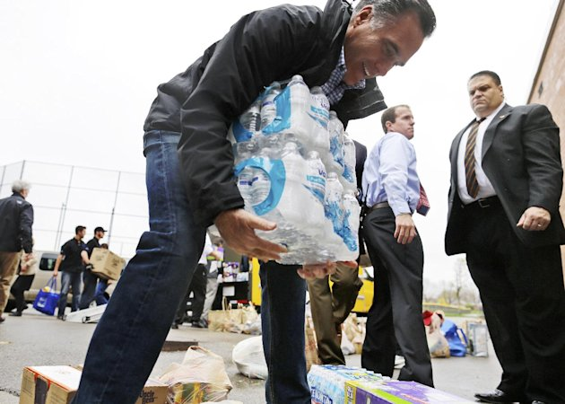 Republican presidential candidate, former Massachusetts Gov. Mitt Romney lifts bottles of water to load into a truck as he participates in a campaign event collecting supplies from residents and local relief organizations for victims of superstorm Sandy,Tuesday, Oct. 30, 2012, at the James S. Trent Arena in Kettering, Ohio. (AP Photo/Charles Dharapak)