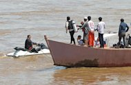 Divers from a Thai rescue team search for bodies after a Lao Airlines plane plunged into the Mekong River, near Pakse town, Laos, on October 17, 2013