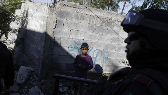 A child looks at a member of the Fuerza Civil police unit during a patrol at an impoverished neighbourhood in Monterrey