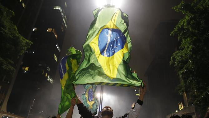 Demonstrators wave their country's national flag on Paulista Avenue where crowds gathered to celebrate the reversal of a fare hike on public transportation, in Sao Paulo, Brazil, Thursday, June 20, 2013. After a week of mass protests, Brazilians won the world's attention and a pull-back on the subway and bus fare hikes that had first ignited their rage. Protesters gathered for a new wave of massive demonstrations in Brazil on Thursday evening, extending the protests that have sent hundreds of thousands of people into the streets since last week to denounce poor public services and government corruption. (AP Photo/Nelson Antoine)