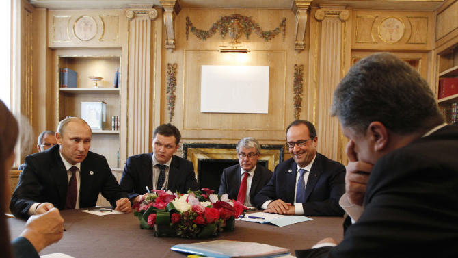 Ukrainian president Petro Poroshenko, right, talks with Russian President Vladimir Putin, left, as French President Francois Hollande watches during a meeting in Milan, Italy, Friday, Oct. 17, 2014. European leaders and Russia signaled cautious optimism over a peace deal for Ukraine after a high-level meeting in Milan on Friday, but emphasized details still need to be worked out. European leaders are pressing Russian leader Vladimir Putin to fully respect a cease-fire deal signed last month in Belarus, which has reduced by not completely ended hostilities in eastern Ukraine.  (AP Photo/Luca Bruno)