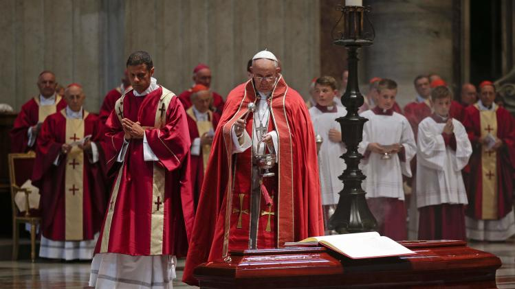 Pope Francis sprinkles holy water over the coffin of Italian cardinal Francesco Marchisano during a funeral service in Saint Peter's Square at the Vatican