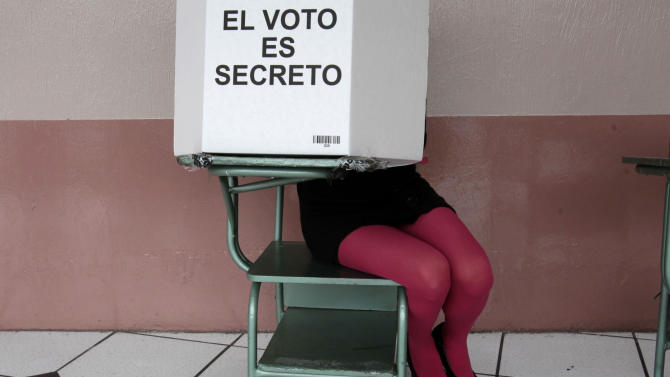 A woman fills her ballot up at a polling station in Quito, Ecuador, Sunday, Feb.17, 2013. Ecuadoreans  elect president,  vice-president and National Assembly members Sunday. President Rafael Correa highly favored to win a second re-election.(AP Photo/Dolores Ochoa)