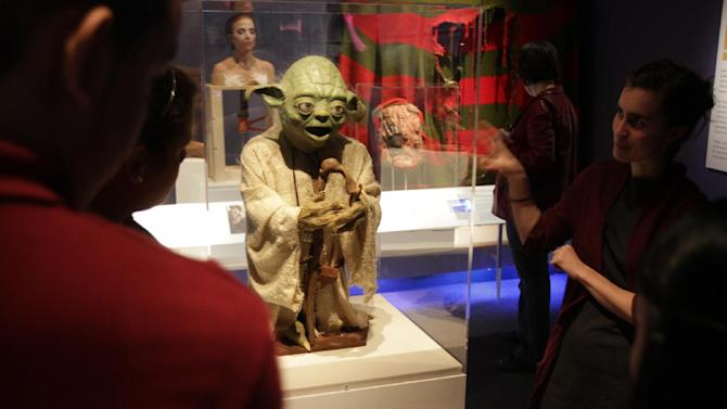 "This undated image provided by the Museum of the Moving Image  shows young visitors encountering Yoda, the ""Star Wars"" character, in the museum's core exhibition ""Behind the Screen,"" in Astoria section of the Queens borough of New York. The artifact, which was a gift to the museum from Stuart Freeborn, is one of a number of items related to popular movies on display at the museum, which also offers hands-on exhibits ranging from old video games to equipment that lets visitors dub their own voices into a scene from a famous film. The Museum of the Moving Image is one of a number of attractions in Astoria and the adjacent neighborhood of Long Island City. Tourists are turning up in Long Island City these days because of a hotel boom there. (AP Photo/Museum of the Moving Image, Brian Palmer)"