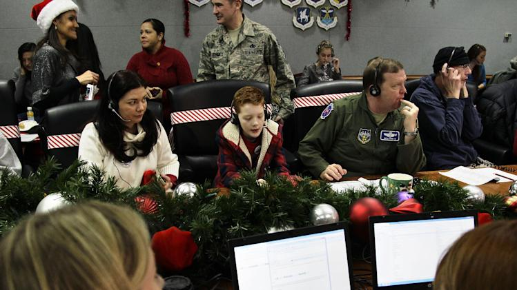 FILE - In this Monday, Dec. 24, 2012 file photo, U.S. Air Force Brig. Gen. Richard Scobie, right, his son Andrew, center, and wife Janis, all take phone calls from children asking where Santa is and when he will deliver presents to their house, during the annual NORAD Tracks Santa Operation, at the North American Aerospace Defense Command, or NORAD, at Peterson Air Force Base in Colorado Springs, Colo. NORAD said Friday, Dec. 28, it drew a record number of phone calls and social media followers during its NORAD Tracks Santa operation on Christmas Eve. (AP Photo/Brennan Linsley, File)