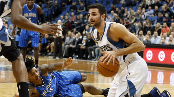 Orlando Magic' Elfrid Payton, lower left, reaches in vain as Minnesota Timberwolves' Ricky Rubio of Spain controls the ball after a collision in the second half of an NBA basketball game, Tuesday, Dec. 1, 2015, in Minneapolis. The Magic won 96-93. (AP Photo/Jim Mone)