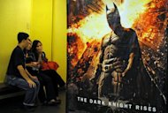 "Filipino movie-goers sit near a Batman poster at a mall in Manila. The Philippines has ordered tighter security at all shopping malls after what it called the ""senseless killings"" of 12 people at a screening of Batman in the United States"