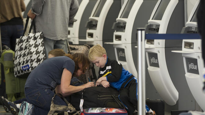 An unidentified woman and her son mark a suitcase at the Jet Blue check-in area in the Fort Lauderdale, Fla. airport, Tuesday, Nov. 20, 2012 as airport officials braced a busy Thanksgiving travel season.  (AP Photo/J Pat Carter)