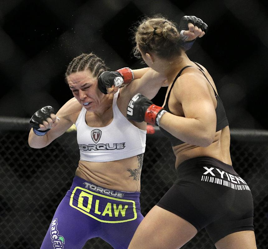 Ronda Rousey hits Alexis Davis during their women's mixed martial arts bantamweight title bout at UFC 175 on Saturday, July 5, 2014, in Las Vegas