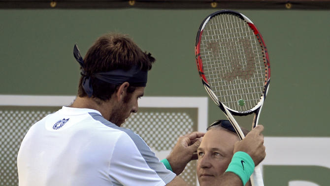Juan Martin del Potro, of Argentina, lifts the glasses of linesman Marcos Cook during his match against Andy Murray, of Great Britain, at the BNP Paribas Open tennis tournament, Friday, March 15, 2013, in Indian Wells, Calif. (AP Photo/Mark J. Terrill)