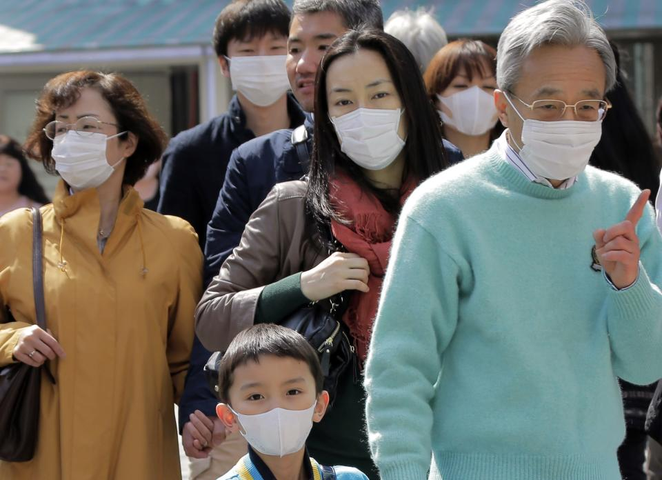 In this photo taken on March 16, 2013, people wearing masks walk down a street in Ginza shopping district of Tokyo. Japan is becoming a sea of surgical masks. It's about pollen, about germs and even a little about China, its polluting rival across the sea. (AP Photo/Itsuo Inouye)