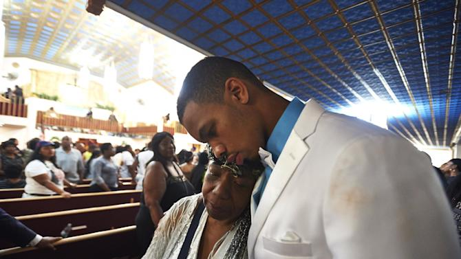 Gwendolyn Flagg-Carr, mother of Eric Garner, and Eric Snipes Garner, Jr., son of Eric Garner, leave his funeral service at Bethel Baptist Church on Wednesday, July 23, 2014, in the Brooklyn borough of New York City. Garner's death while in police custody has led to accusations of police misconduct. (AP Photo/The Daily News, James Keivom, POOL)