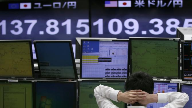 Employee of a foreign exchange trading company works in front of monitors displaying the Japanese yen's exchange rate against the U.S. dollar and against the euro in Tokyo