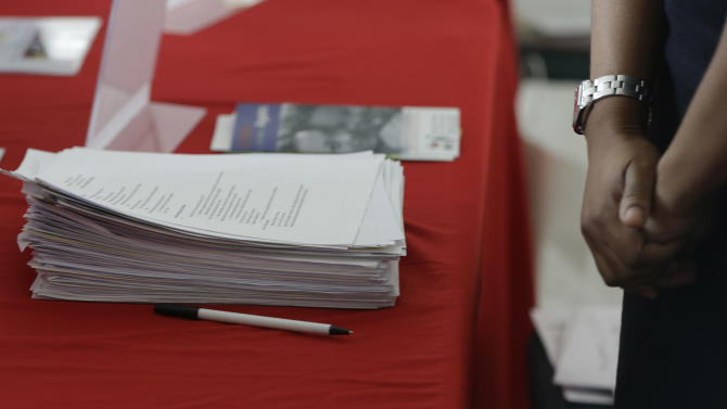 """In this Tuesday, Jan. 22, 2013, photo, Alison Guzman, a recruiter for """"Okey Dokey"""" grocery stores, stands next to a stack of job applications at the job fair in Sunrise, Fla., Tuesday, Jan. 22, 2013. Job fair planners estimated that more 7,500 people attended the event. (AP Photo/J Pat Carter)"""