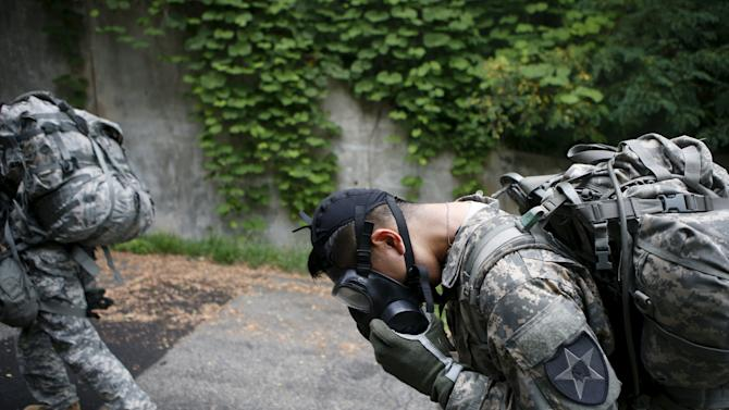 A soldier of the U.S. Army 23rd chemical battalion takes a deep breath under his gas mask as the others march during a competition to test individual soldier skills at Camp Stanley in Uijeongbu