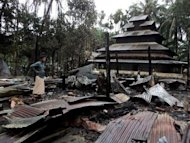 A Bangladeshi man stands amidst the torched ruins of the Buddhist temple called Ramu Moitree Bihar (Ramu Friendship Temple) at Ramu. Sectarian tensions have been running high since June when deadly clashes erupted between Buddhists and Muslim Rohingya in Myanmar's western Rakhine state