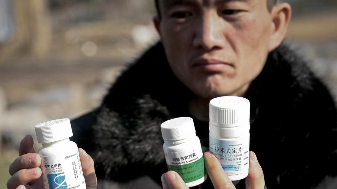 In this Nov. 20, 2012 photo, 28-year-old HIV patient Wang Pinghe shows bottles of medicine pills he has been taking during an interview in Beijing, China. Wang has a tumor in his liver and he wants it surgically removed before it becomes life-threatening, but it will be hard to find a hospital that will do the operation because he has AIDS. In China, hospitals routinely reject people with HIV for surgery out of fear of exposure to the virus or harm to their reputations (AP Photo/Gillian Wong)