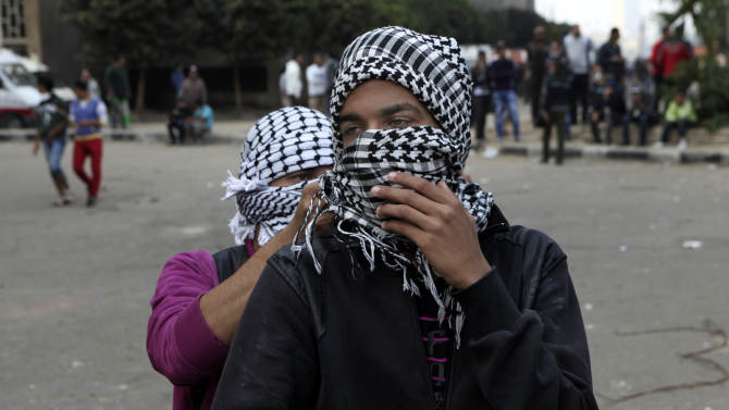 Egyptian protesters wrap themselves in scarves amid tear gas and live ammunition fire during clashes with security forces near Tahrir square, where an opposition rally has been called for to voice rejection of President Morsi's seizure of near absolute powers, in Cairo, Egypt, Tuesday, Nov. 27, 2012. The Health Ministry said 444 people have been wounded nationwide, including 49 who remain hospitalized, since the clashes erupted on Friday, according to a statement carried by the official news agency MENA. (AP Photo/Thomas Hartwell)