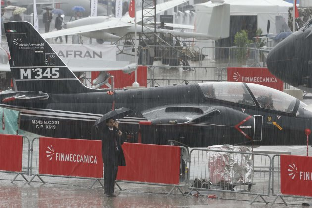 A visitor takes a picture during a rainy day at the 50th Paris Air Show, at the Le Bourget airport near Paris