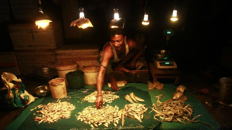 A vendor sorts fish at his stall in a market at Agartala