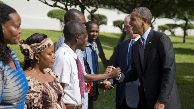 U.S. President Barack Obama, right, and former President George W. Bush shake hands with family members of victims of the U.S. Embassy bombing during a wreath laying ceremony at the U.S. Embassy on Tuesday, July 2, 2013, in Dar Es Salaam, Tanzania. The president is traveling in Tanzania on the final leg of his three-country tour in Africa. (AP Photo/Evan Vucci)