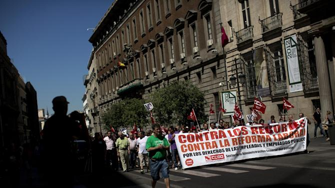 """Civil servants march condemning the recent austerity measures announced by the Spanish government, during a demonstrations in Madrid, Spain, on Friday July 13, 2012.  Spanish civil servants, some dressed in the black of mourning, took to the streets Friday to protest their second wave of wage cuts in as many years as the government prepared to approve austerity measures that include those reductions as part of a deficit-cutting plan to save euro 65 billion through 2015. Placards read in Spanish """"down with tax fraud amnesty"""". (AP Photo/Emilio Morenatti)"""