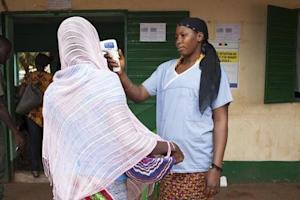 Health worker checks the temperature of a woman leaving …