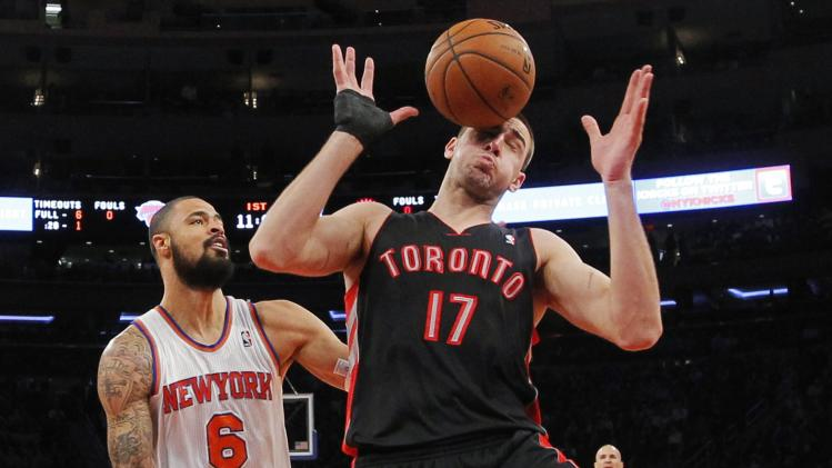 Toronto Raptors' Valanciunas has the ball bounce off his face as he tries to grab a rebound in front of New York Knicks' Chandler during their NBA basketball game in New York