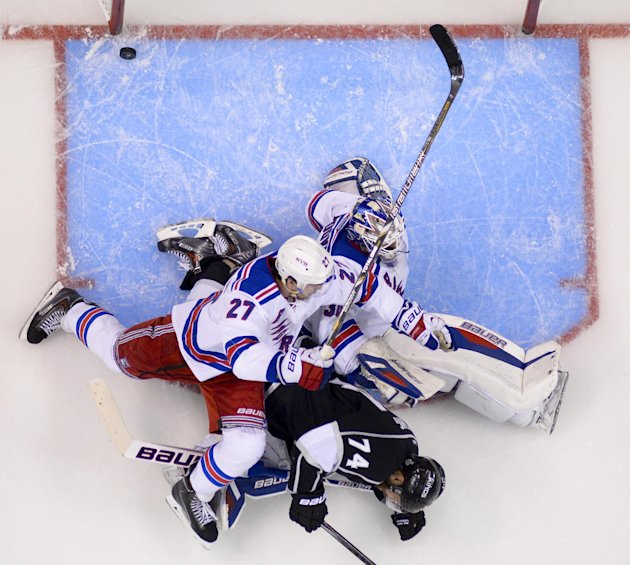 Los Angeles Kings left wing Dwight King, middle, scores between New York Rangers defenseman Ryan McDonagh, left, and goalie Henrik Lundqvist, of Sweden, during the third period of Game 2 in the NHL Stanley Cup Final hockey series in Los Angeles, Saturday, June 7, 2014. (AP Photo/Mark J. Terrill)