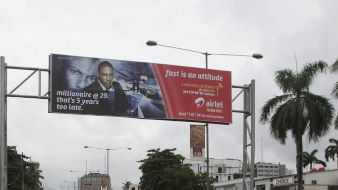 A man pushes his cart  past an advertisement bill board of Bharti Airtel in Lagos, Nigeria, Sunday, May, 1. 2012. Nigeria has fined four mobile phone carriers a total of $7.3 million over poor service and call quality in Africa's dominant market.Reuben Muoka of the Nigeria Communications Commission said Sunday that Bharti Airtel Ltd. of India, Abu Dhabi-based Etisalat, local firm Globacom Ltd. and South Africa-based MTN Group Ltd. all had been fined. (AP Photos/Sunday Alamba)